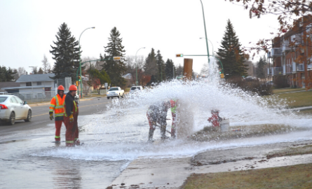 City crews working on a bursting fire hydrant
