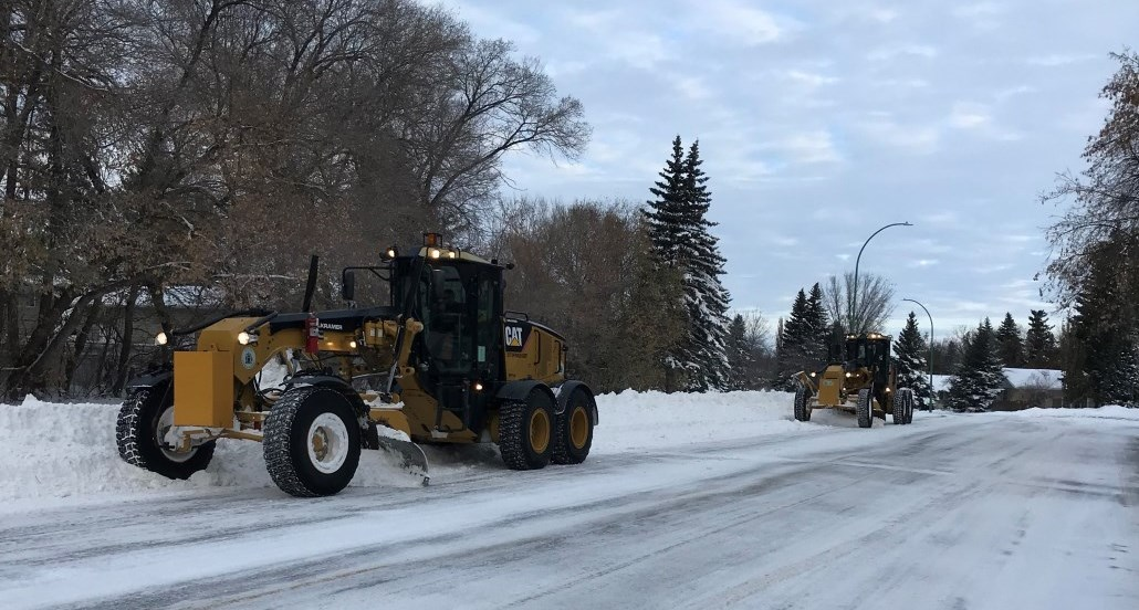 graders clearing a street
