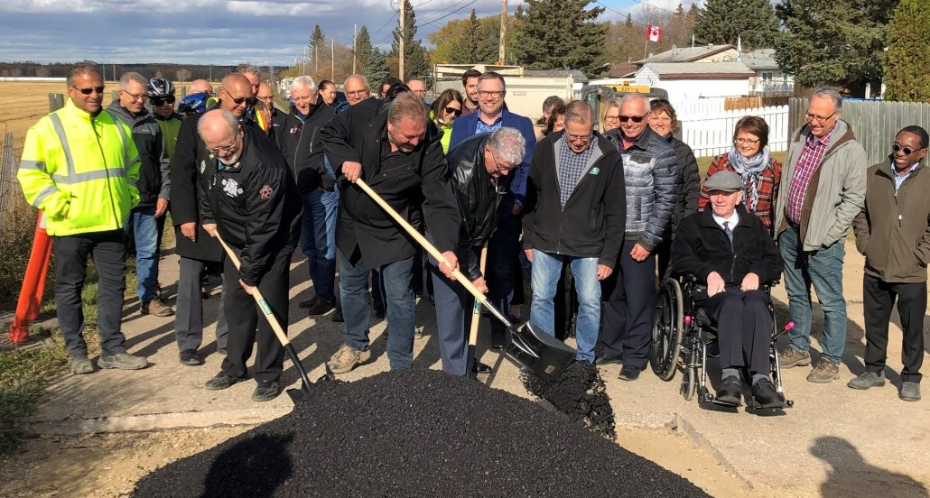Individuals shovel asphalt on the last section of rotary trail