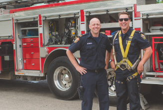 Firefighters smiling by a fire truck