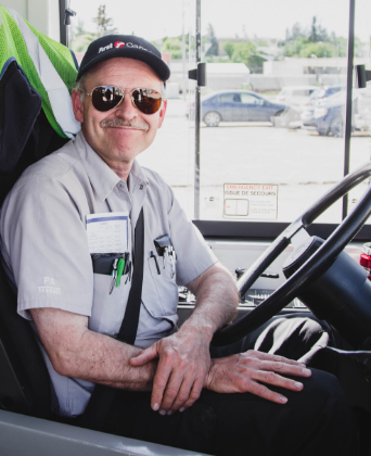 A smiling bus driver