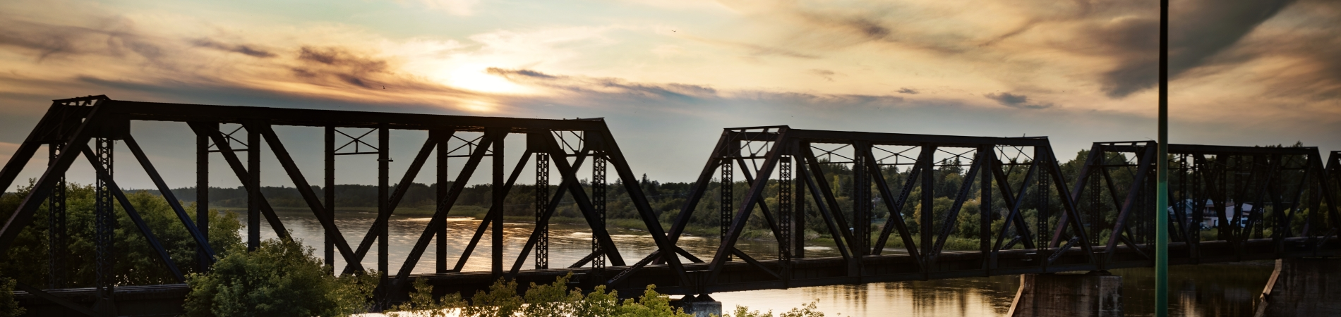 Train bridge over the river at sunset
